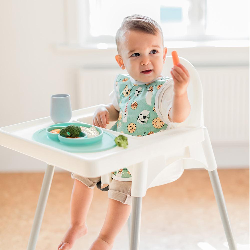 toddler boy eating his lunch out of an ezpz mini mat