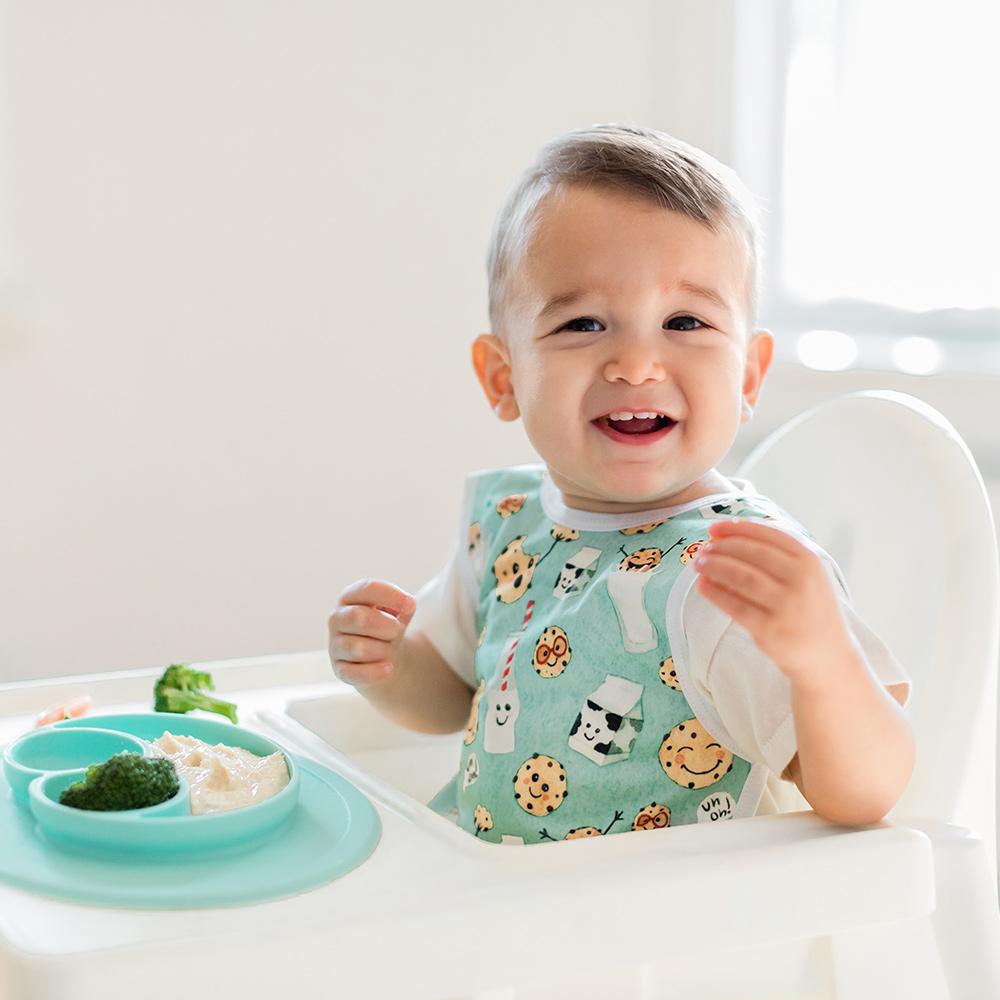 smiling toddler in a high chair eating lunch in an ezpz mat, wearing Bapronbaby bib